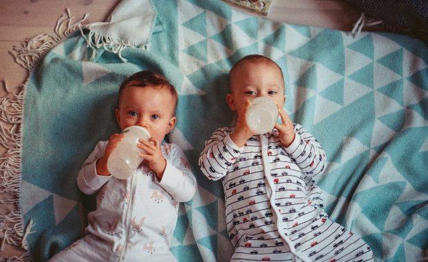 Dos bebés en pijama tomando el biberón.