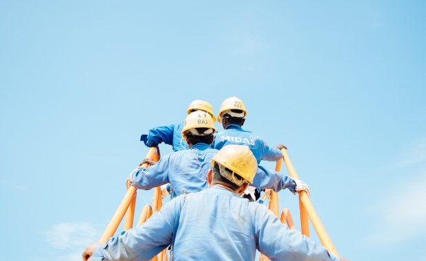 Hombres con ropa laboral subidos en una escalera